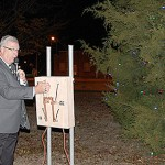 FLIPPING THE SWITCH - Mayor Marvin Sikes rings in the Christmas season by flipping the switch to light up the community Christmas tree at Bailey Park last week. Despite the weather, a good crowd was on hand for the annual tree lighting ceremony.