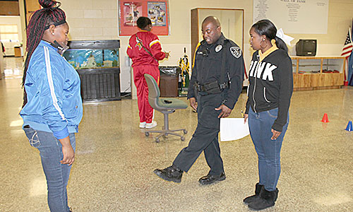 SOBRIETY TEST - School resource officer, Clifton Davis, of the Humboldt Police Department demonstrates to Kadaja Randolph (right) and Kasha Pankey one facet of a field sobriety test. The test uses DUI goggles that impair one's vision to simulate being under the influence of alcohol. Davis teaches criminal justice a Humboldt Jr. & Sr. High School.